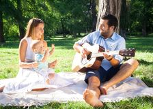 Happy young family spending time outdoor on a summer day. They are enjoy in the sunlight royalty free stock photos