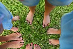 Happy young family spending time outdoor on a summer day. Feet on the grass. Top view royalty free stock photography