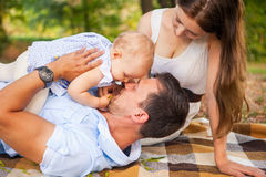 Happy young family spending time outdoor on a summer day, picnic. Happy young caucasian family spending time outdoor on a summer day, picnic in the park. Set stock photos