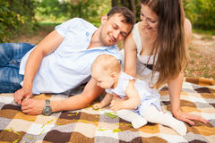 Happy young family spending time outdoor on a summer day, picnic. Happy young caucasian family spending time outdoor on a summer day, picnic in the park. Set stock photography