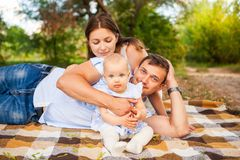 Happy young family spending time outdoor on a summer day, picnic. Happy young caucasian family spending time outdoor on a summer day, picnic in the park. Set royalty free stock photo
