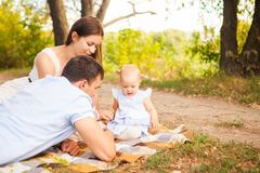 Happy young family spending time outdoor on a summer day, picnic. Happy young caucasian family spending time outdoor on a summer day, picnic in the park. Set stock images