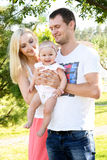 Happy young family spending time outdoors on a summer day. Royalty Free Stock Images
