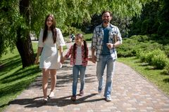 Happy young family spending time in park on summer day. Walking On Path. Happy Family Concept royalty free stock photography