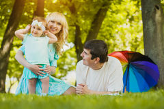 Happy young family spending time on a summer day. Young family spending time outdoor on a summer day stock photo
