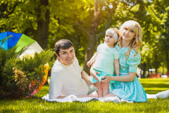 Happy young family spending time on a summer day. Young family spending time outdoor on a summer day royalty free stock images