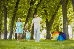 Happy young family spending time in sunny park. Young family spending time outdoor on a summer day royalty free stock photography