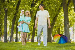 Happy young family spending time in sunny park. Young family spending time outdoor on a summer day royalty free stock image
