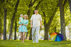 Happy young family spending time in sunny park. Young family spending time outdoor on a summer day stock images