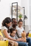 Happy young family spending time together with devices. On cozy couch Stock Photo