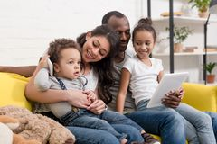 Happy young family spending time together with devices. At home royalty free stock photo
