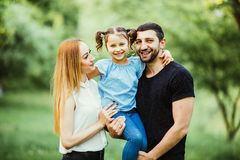 Happy young family spending time together in green nature. wife with husbend and daughter. Mother and father holding daughter in p. Happy family spending time stock photos