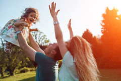 Happy young family spending time together outside in green nature. Beautiful happy family spending time together outside in green nature. Father throwing his royalty free stock photo