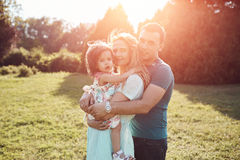 Happy young family spending time together outside in green nature. Beautiful happy family spending time together outside in green nature. Sunlight effect royalty free stock photography