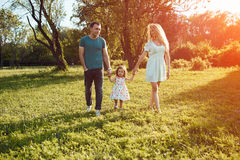 Happy young family spending time together outside in green nature. Beautiful happy family spending time together outside in green nature. Sunlight effect stock images