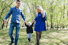 Happy young family spending time together outside in green nature stock images