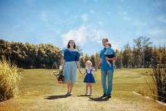 Happy young family spending time together outside in green nature. Family goes on a picnic on a autumn day royalty free stock image