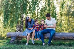 Happy young family spending time together outside in green nature. Parents playing with twins outside. stock photos