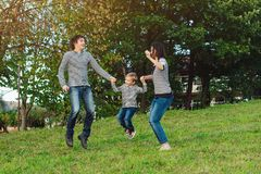 Happy young family spending time together in park. Happy young family spending time together in a park royalty free stock photography