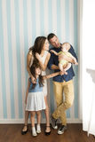 Happy young family. Young family standing side by side by the wall stock photography