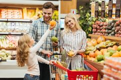 Happy young family standing with a trolley. And choosing ts at the supermarket Royalty Free Stock Images