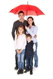 Happy young family standing under one umbrella Royalty Free Stock Photography