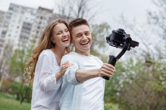 Happy young family taking video selfies with her camera on the gimbal steadycam. Happy young family taking selfies with her camera on the gimbal steadycam Stock Photography
