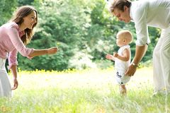 Happy young family teaching baby to walk. Portrait of a happy young family teaching baby to walk in the park stock images