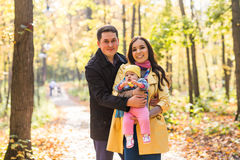 Happy young family with their daughter spending time outdoor in the autumn park. royalty free stock images