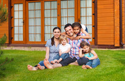 Happy young family with three children. Inear the house Royalty Free Stock Photos