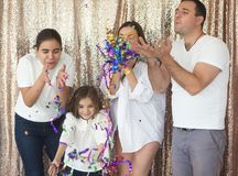 Happy young family having fun with confetti stock image