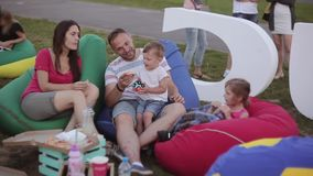 Happy young family with two kids resting on a picnic at the park. Boy and girl eating pizza, sitting in bean bag chairs stock video footage
