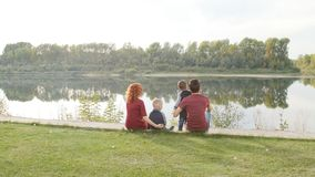 Happy young family with two sons walks and rests in a park by the river. Family and relationship concept