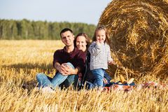 Happy young family with two year old girl next to hay bales. In harvested field Stock Images