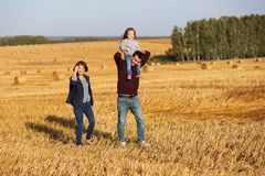Happy young family with two year old girl walking in a field Royalty Free Stock Images