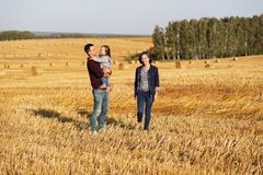 Happy young family with two year old girl walking in a field Stock Images