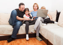 Happy young family using laptop. On the couch or sofa in the living room Stock Photography