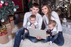Happy young family using a laptop pc. At home by a fireplace in warm and cozy living room on winter day Stock Images