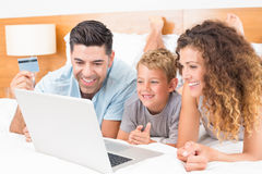 Happy young family using laptop to shop online together on bed Stock Images
