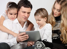 Happy young family using a tablet computer Stock Images