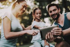 Happy Young Family Using Tablet in Summer Park. stock photo