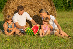 Happy young family on vacation. The family from four people has rest outdoors with water-melon near haystack Stock Photos