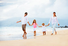 Happy young family walking on the beach stock images