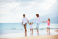 Happy young family walking on the beach stock photography