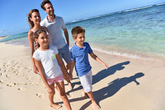 Happy young family walking by crystal clear seawater Stock Photos