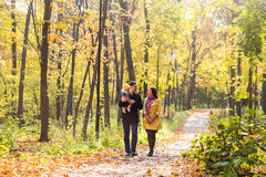 Happy young family walking down the road outside in autumn nature. Royalty Free Stock Images