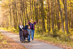 Happy young family walking down the road outside in autumn nature. Royalty Free Stock Image