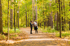 Happy young family walking down the road outside in autumn nature. Royalty Free Stock Photos