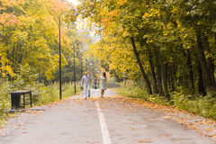 Happy young family walking down the road outside in green nature. Royalty Free Stock Photo