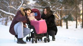Happy, young family walking, making photos in a winter park, mom, dad and baby in stroller. Man is making selfie wirh stock photo